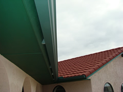 Guttering installed on slanted fascia and tile roof using wedges